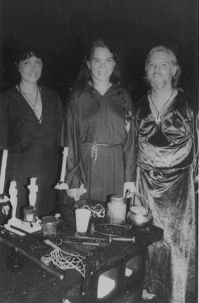 Three smiling Witches standing behind a small altar.