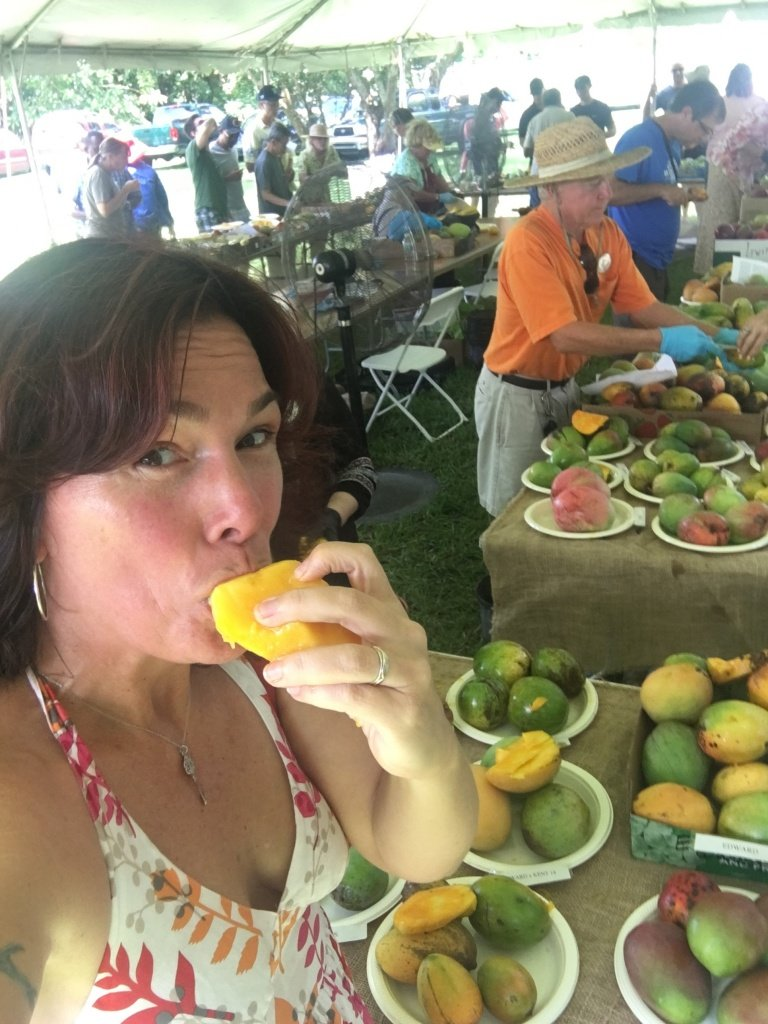 Woman eating a mango.